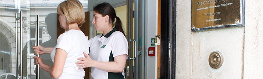 Liverpool OT therapist helps a patient with a door as they enter the clinic.