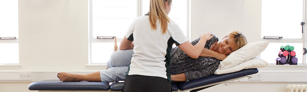 Liverpool OT patient lies down during therapy while Liverpool OT therapist aids her.
