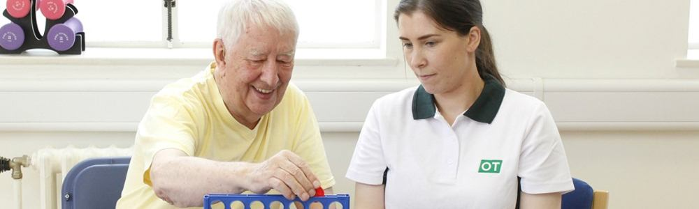 Liverpool OT plays a game of connect four with happy client during therapy.