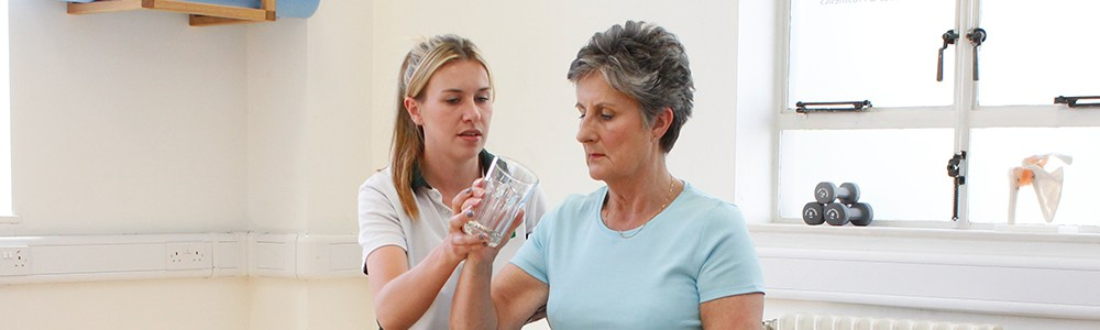 Experienced Liverpool OT therapist helps patient with a glass of water.