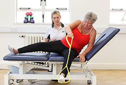 Liverpool OT patient uses resistance band to stretch leg during therapy.