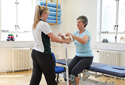 Experienced Liverpool OT helps patient stand up using physical aid.