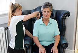 Liverpool OT therapist shows patient how to adjust her posture while seated.